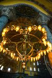 ISTANBUL, TURKEY: Hagia Sophia interior. Old metal chandelier with light bulbs between columns. Hagia Sophia is the greatest monument of Byzantine Culture royalty free stock photo