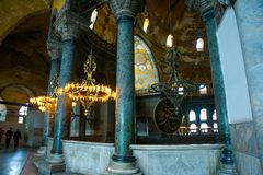 ISTANBUL, TURKEY: Hagia Sophia interior. Old metal chandelier with light bulbs between columns. Hagia Sophia is the greatest monument of Byzantine Culture royalty free stock photography