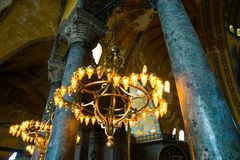 ISTANBUL, TURKEY: Hagia Sophia interior. Old metal chandelier with light bulbs between columns. Hagia Sophia is the greatest monument of Byzantine Culture royalty free stock image