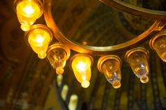 ISTANBUL, TURKEY: Hagia Sophia interior. Old metal chandelier with light bulbs. Hagia Sophia is the greatest monument of Byzantine Culture stock image