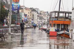 Istanbul Turkey January 31 2019: A man walking down the docks on rainy day. Orange transportation boat is moored on the docks. stock photo
