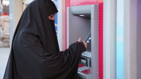 ISTANBUL,TURKEY - JANUARY 2014: Woman with headscarf using ATM machine stock video footage
