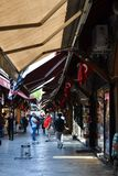 ISTANBUL, TURKEY - july 10, 2017: People shopping in the Grand Bazar, handmade pillows, bags and carpets are on the wall royalty free stock photography