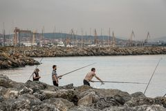 Friends Fishing from the Rocks at Seaside. ISTANBUL, TURKEY - JUN 06, 2012: Friends fishing from the rocks at seaside royalty free stock images