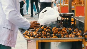 Istanbul, Turkey - June 12, 2019: male salesman is cooking Roasted chestnuts on a city street. Street food, the hot stock video
