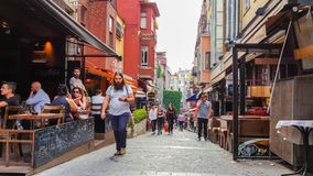 Istanbul, Turkey - June 02, 2017: People walking in a narrow street filled with bars in Kadikoy, Istanbul. Royalty Free Stock Photos