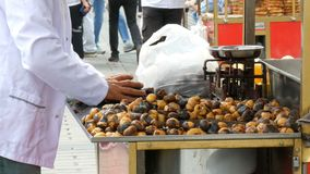 Istanbul, Turkey - June 12, 2019: Roasted chestnuts on a city street. Street food, the hot cooked chestnuts stock video