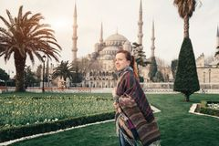 Blue mosque of Istanbul and young traveler in foreground. Istanbul, Turkey - March 31, 2017: Famous Sultan Ahmet Blue Mosque is popular architectural and Royalty Free Stock Images