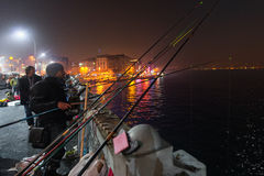 ISTANBUL, TURKEY - NOV 19: Local fishermen fishing on the Galata Bridge at night that crosses the Golden Horn in Istanbul on stock images