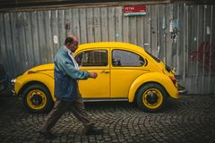 man walking by yellow vintage volkswagen kafer near fence royalty free stock images