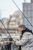 Istanbul Turkiet/April 1, 2016 - mannen förbereder hans stång för att fiska av bron royaltyfria foton