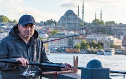 Istanbul Turkiet/April 30, 2016 - mannen fiskar av en pir arkivfoto