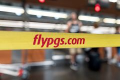ISTANBUL TURKIET - Juli 28, 2017: Gult band med logo av Pegasus Airlines på den internationella Istanbul Ataturk flygplatsen Fotografering för Bildbyråer