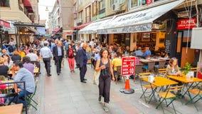 Istanbul Turkiet - Juni 02, 2017: Folk som förutom äter på de touristic restaurangerna i gamla Kadikoy gator Arkivfoto