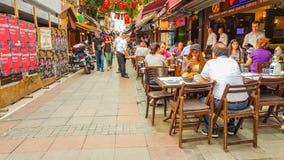 Istanbul Turkiet - Juni 02, 2017: Folk som förutom äter på de touristic restaurangerna i gamla Kadikoy gator Arkivbilder