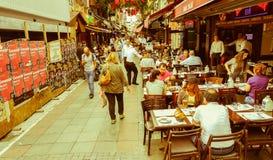 Istanbul Turkiet - Juni 02, 2017: Folk som förutom äter på de touristic restaurangerna i gamla Kadikoy gator Arkivbild
