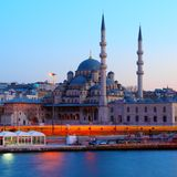 Istanbuls New Mosque at night. Istanbul with its New Mosque seen from the sea at night with traffic blurs Royalty Free Stock Image