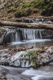 Istapp djupt i skogen med vattenfallet Arkivbilder