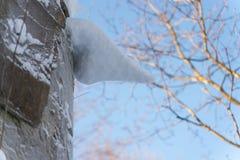 Istapp på betongväggen som täckas med snö arkivbild