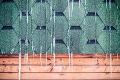 Istapp som hänger på ett tak av trähuset Fotografering för Bildbyråer