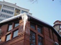 Istappar hänger från taket av byggnad Fara för förbipasserande, hot av död och skada från istappar royaltyfri bild
