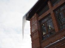 Istappar hänger från taket av byggnad Fara för förbipasserande, hot av död och skada från istappar Vinterhot arkivfoto