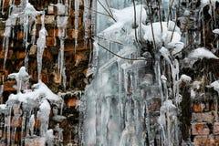 Istappar isför mycket på bakgrunden av en tegelstenvägg, för tegelstenvägg för closeup abstrakt gammal bakgrund med sprickais, mo Royaltyfri Bild