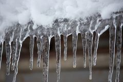 Istappar och snö på takcloseupen Vinterväderbegrepp Fryste och isbakgrund Snö och istapp iced över waterside arkivfoto