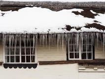 Istappar på ett halmtäckt tak Arkivfoto