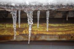 Istappar på tappningtakcloseupen Vinterväderbegrepp Fryste och isbakgrund Snö och istapp iced över waterside royaltyfri fotografi