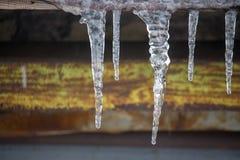 Istappar på tappningtakcloseupen Vinterväderbegrepp Fryste och isbakgrund Snö och istapp iced över waterside royaltyfri foto