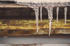 Istappar på tappningtakcloseupen Vinterväderbegrepp Fryste och isbakgrund Snö och istapp iced över waterside royaltyfria foton