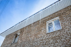 Istappar som hänger från taket av tegelstenbyggnad Frostigt mönstrar Royaltyfri Fotografi