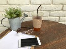 Iste i plast- exponeringsglas, exponeringsglas, smartphones och dokument på den wood tabellen bredvid den vita väggen med begrepp Royaltyfri Fotografi