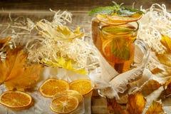 Iste med citronfärgstänk Varmt gult te med citronen och många sl royaltyfria bilder