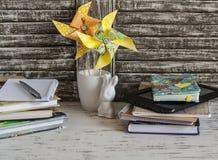 Istituto per l'infanzia l'area di lavoro con le girandole dei libri, dei taccuini, dei blocchi note, della compressa e della cart Fotografia Stock