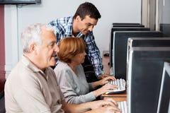 Istitutore Assisting Senior Woman nel per mezzo del computer Fotografia Stock