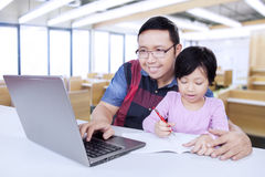 Istitutore che per mezzo del computer portatile mentre insegnando al suo studente Fotografia Stock