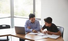 Istitutore Giving Male Student della High School con l'insegnamento dei computer portatili uno - uno allo scrittorio immagine stock