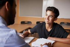 Istitutore insegnamento di Giving Male Student uno - uno della High School allo scrittorio immagini stock