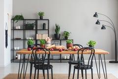 Istna fotografia wygodny jadalni wnętrze z stołem, czarna półka w tle pełno, i zdjęcie stock