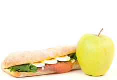 Istna kanapka z uwędzonym łososiem, jajkami i zielonym jabłkiem na białym tle. Zdjęcia Royalty Free