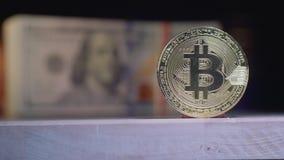 Istni złocistej monety Bitcoin stojaki przeciw tłu chodzenie paczki Amerykańscy dolary zbiory wideo