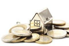 Istny estade tło, mały dom w rozsypisku monety odizolowywać obraz stock