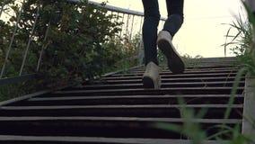 Istot ludzkich nogi ubierać w cajgach i kuć w starych sneakers iść w górę plenerowych metali schodków w zielonym poroślu osamotni zdjęcie wideo