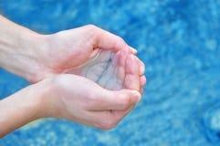 Istota ludzka wręcza chełbotanie wodę Obrazy Royalty Free