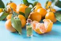 Istotny olej pomarańczowa mandarynka w szklanej butelce nad pastelowym błękitnym tłem Skincare pojęcie zdjęcia royalty free