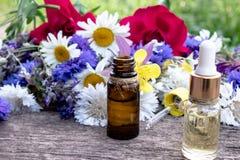 Istotny olej w szklanej butelce blisko wildflowers na drewnianym tle obraz stock