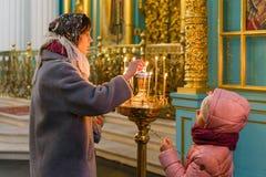 ISTRA, RUSSIE - 23 mars 2019 : Le nouveau monastère de Jérusalem La jeune femme et sa fille ont mis des bougies dans le chandelie photos stock