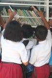 istruisca gli studenti che leggono un libro nella biblioteca mobile Immagini Stock Libere da Diritti